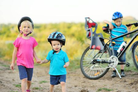 small children-boy and girl brother and sister in Bicycle helmets are holding hands on the background of a Bicycle.