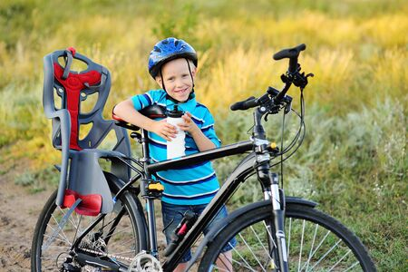 a small child-a boy in a Bicycle helmet with a bottle of water in his hands smiling holding a large adult mountain bike