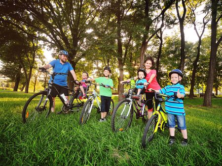 a group of people on bicycles - two adults and four young children in Bicycle gear and helmets against the background of trees, Park and green grass. Family and active lifestyle.family Day