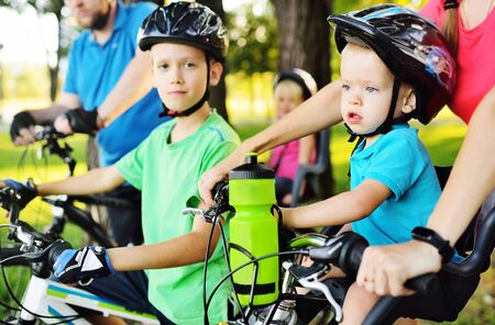 a small child a boy in equipment and a helmet sits in a childrens Bicycle seat near his parents