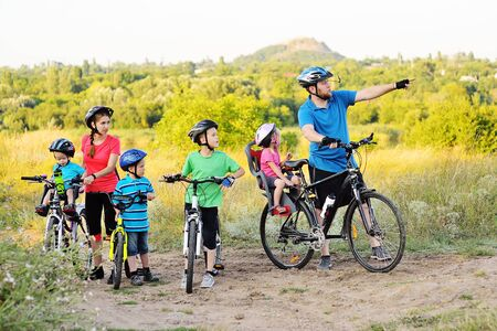 a group of people on bicycles - two adults and four young children in Bicycle gear and helmets against the background of trees, Park and green grass. Family and active lifestyle.