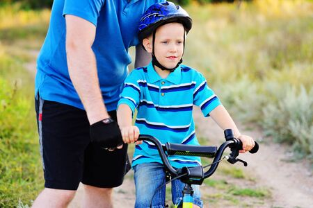 A father teaches a small child of a son in a protective helmet to ride a Bicycle. Zdjęcie Seryjne