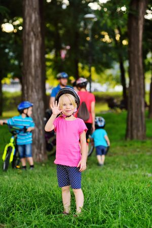 a child-a little girl in a pink t-shirt and a protective Bicycle helmet smiles and waves against the background of her parents