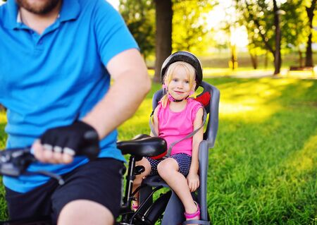 a man dad in a sports uniform carries a little girl daughter on a Bicycle in a childrens Bicycle seat.
