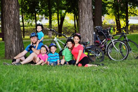 a large family-mom, dad and a group of small children sitting on the grass in Bicycle gear and helmets smiling against the background of bicycles, Park and green grass.