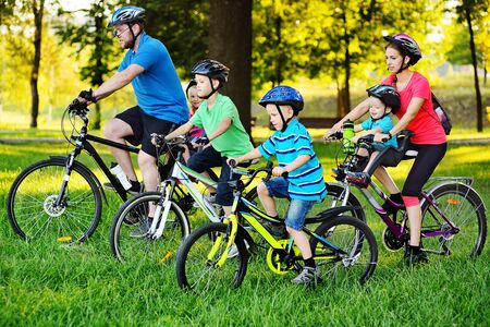 Young large family on bicycles in the Park against the background of greenery and trees.family Day
