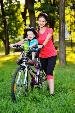 a small child in a protective helmet smiles sitting on a childs Bicycle seat on a large mountain bike with his mother on the background of green grass and nature. Active lifestyle, sports, childhood Zdjęcie Seryjne