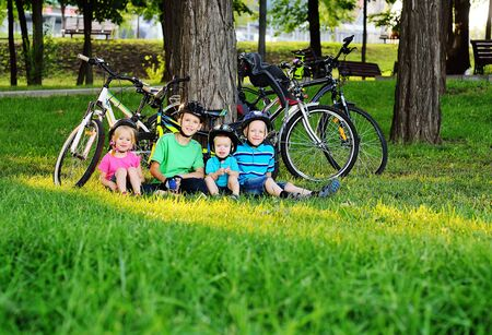 a group of small preschool children in Bicycle safety helmets smile sitting on the fresh green grass in the Park