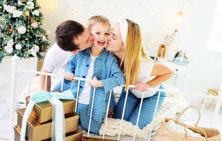 young family - mom, dad and little son in pajamas sitting on the bed against the background of a Christmas tree with gifts hugging and smiling.