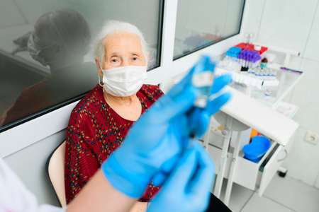 a nurse wearing a mask and rubber gloves is preparing to vaccinate an elderly woman against viral diseases. Prevention of virus infection Standard-Bild