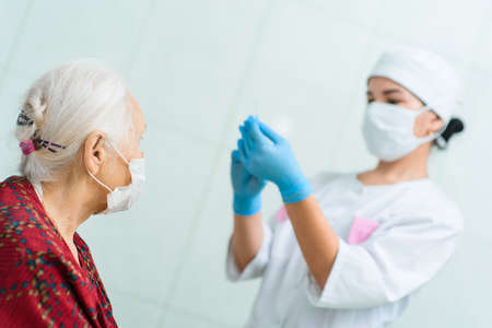 A doctor wearing rubber gloves prepares to inject an elderly woman in the hospital. A nurse holds a syringe before making a vaccine Standard-Bild