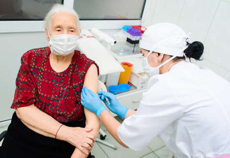a doctor or nurse injects a drug or vaccine into an elderly woman's shoulder. Standard-Bild