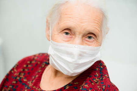 a large-faced portrait of an elderly woman with gray hair and sad eyes wearing a medical mask. Quarantine, disease, risk group Standard-Bild