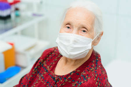 a large-faced portrait of an elderly woman with gray hair and sad eyes wearing a medical mask. Quarantine, disease, risk group, infection.
