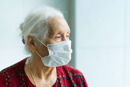 An elderly woman of 70-80 years old with gray hair and sad eyes in a medical mask stands at the window. Old age, illness, loneliness, old people.