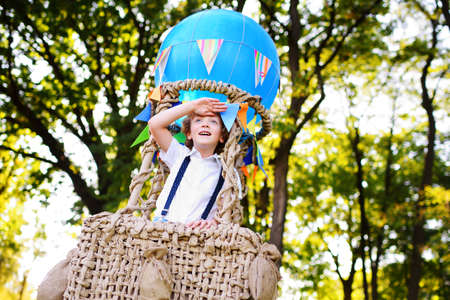 a child a small boy with curly hair in a basket of a blue balloon smiles and looks into the distance against the background of greenery and the sun.