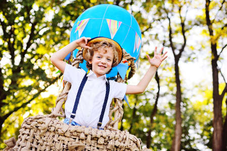 a little boy with curly hair in a straw hat in a balloon basket is smiling and enjoying the journey. Childhood, dreams, fantasies