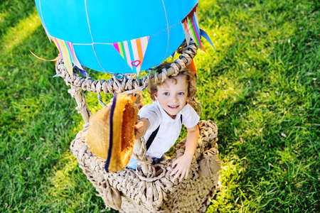 a little boy with curly hair in a straw hat sitting in a basket of a blue balloon smiles against the background of grass and gets ready to fly.