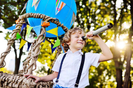 a small boy with curly hair with a spyglass, in his hands against the background of a blue balloon basket smiles and looks into the distance.