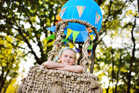 a little girl smiles as she sits in the basket of a blue balloon