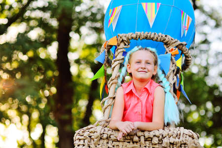 a little girl in pink clothes smiles sitting in a basket of a blue balloon against a background of sunlight and greenery.