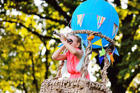 a little girl in pink clothes with a spyglass in her hands in the basket of a blue balloon looks into the distance and smiles.