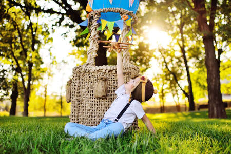 a little boy in a white shirt with suspenders with curly hair in a pilots hat and glasses plays with a wooden plane against the background of a basket with a blue balloon. Standard-Bild