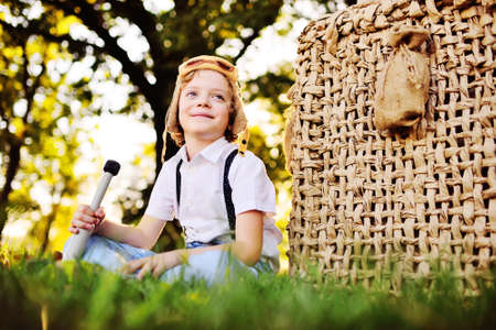 a small boy in a white shirt with suspenders and wearing a pilots helmet with glasses smiles as he sits on the grass leaning on a balloon basket against the background of trees
