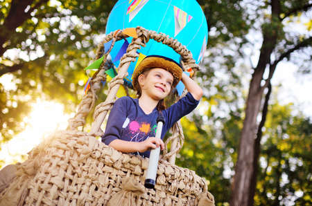 a cute little girl in a straw hat is smiling in a balloon basket. Childhood, adventure