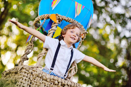 a child a small boy with curly hair in a basket of a blue balloon smiles Standard-Bild