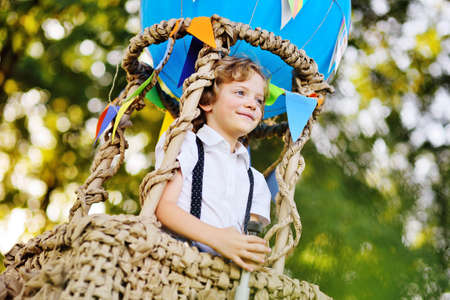 a small boy with curly hair with a spyglass in his hands against the background of a blue balloon basket Standard-Bild