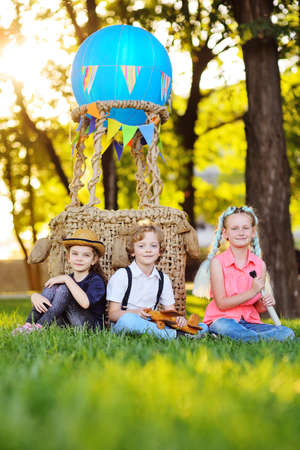 three small preschool children sit on the grass against the background of a basket of blue balloons and sunlight. Childhood, adventure, vacation. Standard-Bild