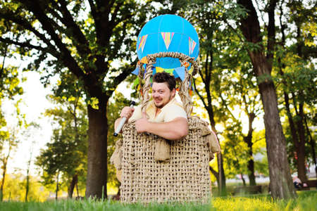 a large adult bearded man in the basket of a toy balloon. Return to childhood, eternal child, dreamer.