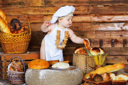 baby boy in a chefs hat and apron with a bunch of bagels around his neck sits against the background of bakery products in a bread shop. Zdjęcie Seryjne