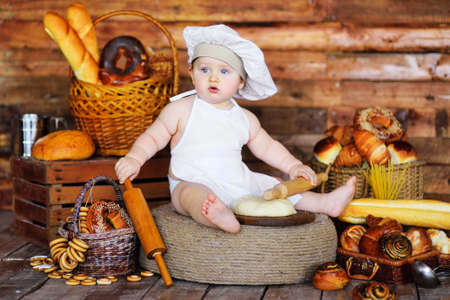 baby baker boy in a chefs hat and apron rolls out raw dough with a wooden rolling pin against the background of bakery products. Zdjęcie Seryjne