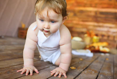 baby boy in a white chefs apron crawls across the wooden floor for a bagel.