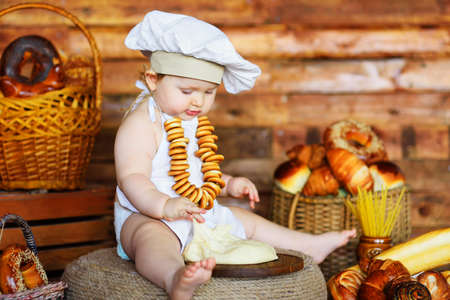 baby baker boy in a chefs hat and apron with a bunch of bagels around his neck prepares dough for baking against the background of bakery products.