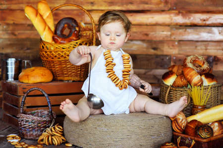 boy cook in an apron holding a whisk and ladle on the background of bakery products.