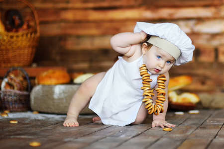 baby boy in a chefs hat and apron with a bunch of bagels around his neck on a wooden background