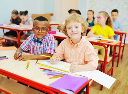 two small children of elementary school students are preparing for a lesson sitting at a Desk with colored pencils in their hands