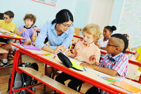 young woman teacher helps children to do the job in the classroom in primary school. Zdjęcie Seryjne