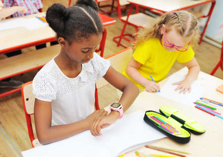 a little African-American girl sitting at a Desk in a primary school looks at a smart watch on her hand against the background of the school class and children. Zdjęcie Seryjne