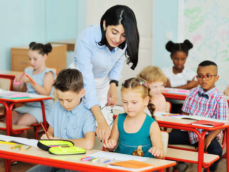 a young female teacher helps young children students with solving tasks against the background of a modern classroom in an elementary or primary school. Back to school