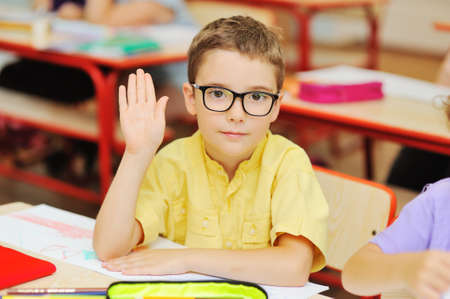 small child schoolboy in a yellow shirt and glasses reaches out for a response in the background of a primary school classroom. Back to school.