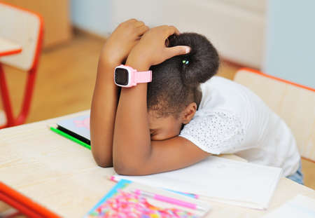 a tired African-American school girl with a smart watch on her hand is sleeping or resting while sitting at a Desk.