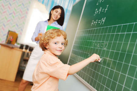 a cute little boy schoolboy with curly hair writes with chalk on the blackboard and decides a mathematical example together with a female teacher on the background of the classroom.