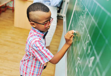 a small child an African-American schoolboy with red glasses writes with chalk on a green blackboard against the background of a female teacher in an elementary school.