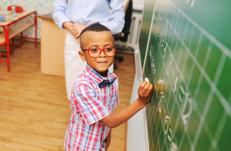little schoolboy African American with glasses writing with chalk on the blackboard against the teacher.