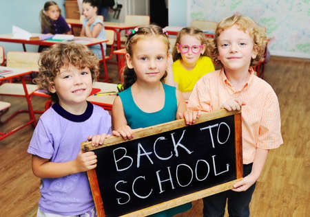 group of school children smiling holding a sign that says