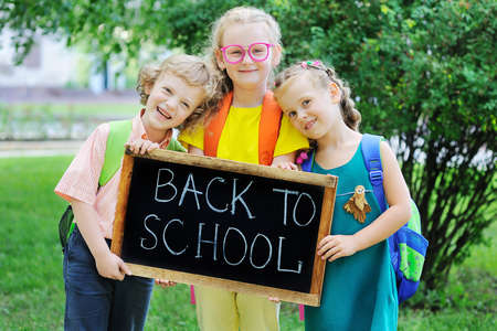 a curly-haired boy and two girls with school bags-smile and hold a sign that says